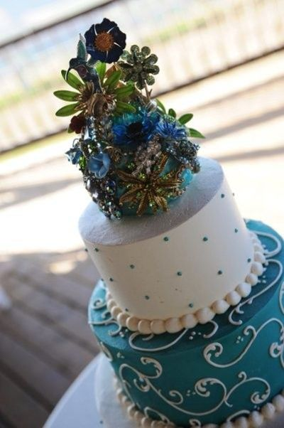 Brooch bouquet on top of wedding cake, wow.
