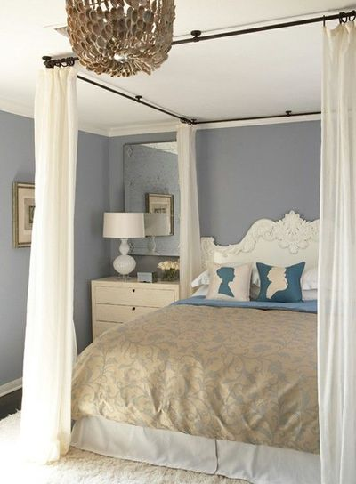 Ceiling mounted curtain rods to create a canopy on a traditional bed without posters.