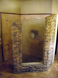 Angled rock shower wall with striated glass.