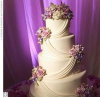 white swag cake with bouquets