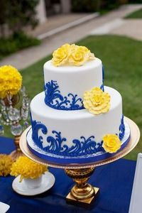 Wedding cake with blue accents and yellow flowers. Love!